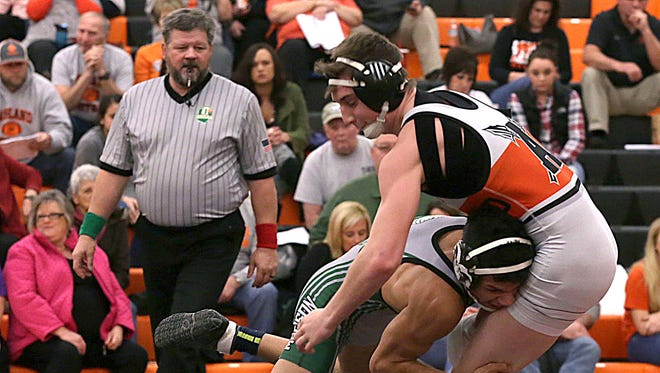 Tom Stortz officiates a wrestling match between Madison's LeConte Merrell and Ashland's Landon Plank during a meet at Ashland High School on January 25, 2017.