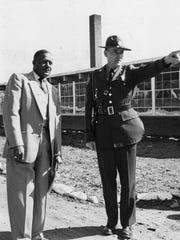 Principal C.U. James in 1954 hosts a State Highway Patrol officer at the Carver Center.