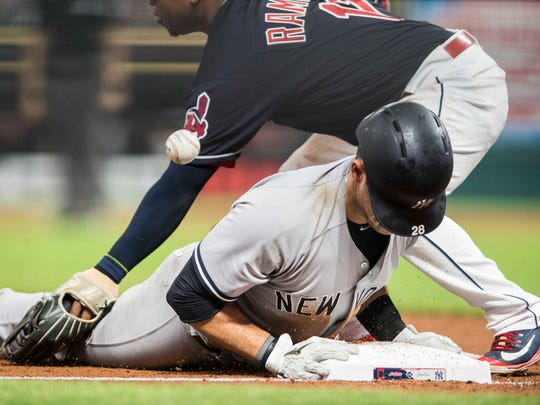 Jul 14, 2018; Cleveland, OH, USA; New York Yankees catcher Austin Romine (28) slides into third base as Cleveland Indians third baseman Jose Ramirez (11) misses the ball during the seventh inning at Progressive Field. Romine was credited with a double and then went home on the play as the Indians were charged with two errors.