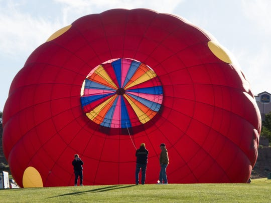 A hot air balloon participating in the 13th annual Page Lake Powell Hot Air Balloon Regatta is prepared for takeoff at the Lake Powell National Golf Course in Page Sunday, Nov. 8, 2015. A weekend filled with fantastic ballooning weather saw 60 hot air balloons filling the skies over Lake Powell on Friday, Saturday and Sunday mornings. In additions, about 20 of the balloons were lined up along Lake Powell Boulevard Saturday night for a balloon glow and street festival.
