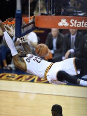LeBron James dunks off an alley-oop pass from JR Smith