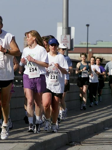 The dome of the Stearns County Courthouse looms as a seemingly endless stream of runners cross the Veterans Bridge over the Mississippi River in April 2000 during the Earth Day Half-Marathon in St. Cloud. Some 445 runners were credited with finishing.