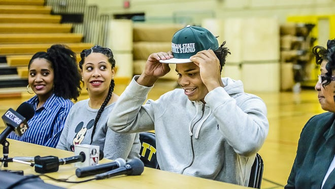 Miles Bridges puts a hat on while being flanked by his two sisters, left, and his mother Cynthia on Saturday during a news conference at Mott Community College in Flint. Cynthia Bridges said she sent Miles to Huntington Prep in West Virginia after his freshman year of high school to escape a bad crowd and the violence in Flint.