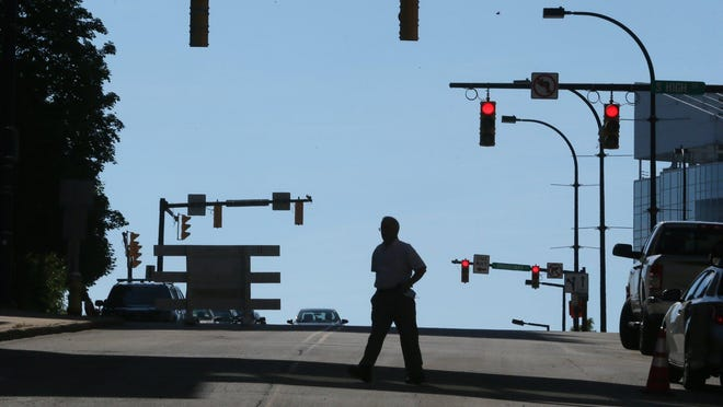 Walid Qaqish crosses University Avenue on his way to Main Street while running an errand in downtown Akron on Monday.