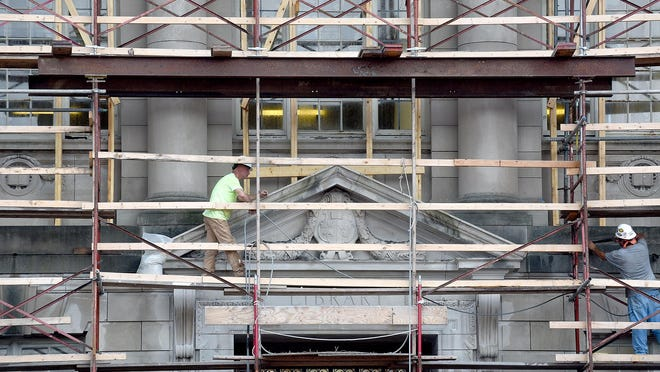 Workers pressure wash the front of Ellis Library on Lowry Mall on Wednesday at the University of Missouri as part of a maintenance and repair project where windows on the north and west sides of the building will be replaced.