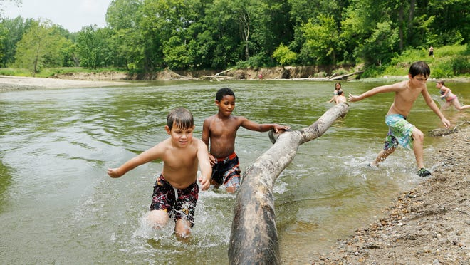 Brothers Luke Pendley, 6, from left, Tony, 7, and Eli, 10, race to a log they were using as a springboard while swimming Wednesday in Wildcat Creek at Wildcat Park. The park was populated by children and adults, who were seeking relief from the warm, humid weather.