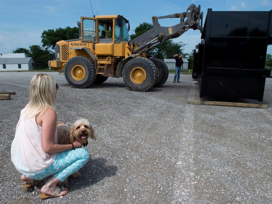 Brittany Hazelwood and her dog, Copper, check on the arrival of three new dumpsters at Braco, a roll-off dumpster business in Henderson Friday morning. Preston Roberts used the lift to hold the inside dumpster up as David Wicker directed him.