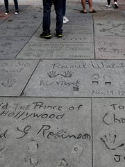 In this May 9, 2017 photo, tourists look at the hand and footprints of celebrities in the forecourt of the TCL Chinese Theatre in the Hollywood section of Los Angeles. The storied Hollywood Boulevard movie palace, originally named Grauman's Chinese Theatre, opened its doors on May 18, 1927. (AP Photo/Jae C. Hong)
