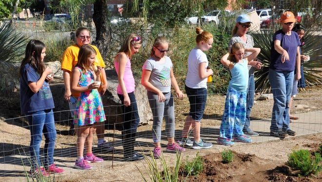 Trish Cutler, right, a wildlife biologist with the Environmental Stewardship Branch at White Sands Missile Range, shows members of Girl Scout Troop 546 where they will be working to help with a Pollinator Habitat Garden.