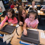 Teacher Kami Russell, center, assists students, Isabella Musacchia, left, Amberly Helms-Patterson, right, with a computer assignment at S.S. Dixon Primary School in Pace. Dixon, has over 700 kindergarten through second grade students, and like many other Santa Rosa County schools is at or near capacity.