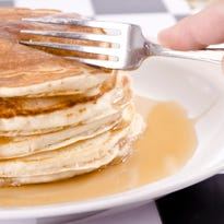 Rufino Sanchez, an employee of the Brick IHOP, serves pancakes during a past National Pancake Day