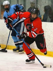 Digging the puck out of the corner for Livonia Churchill is junior forward Josh Friend.