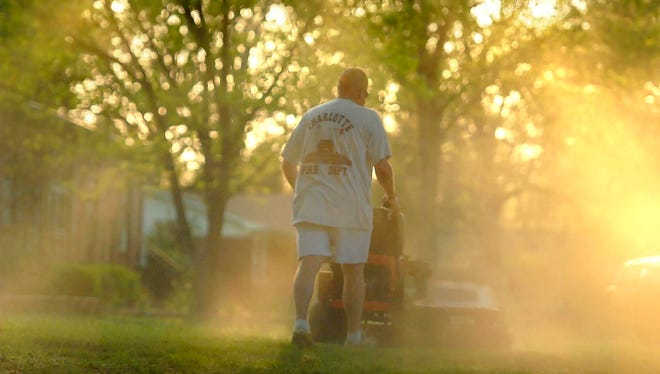 Shane Nantz kicks up a cloud of pollen as he mows the front yard of his west Charlotte, N.C., home in 2010.