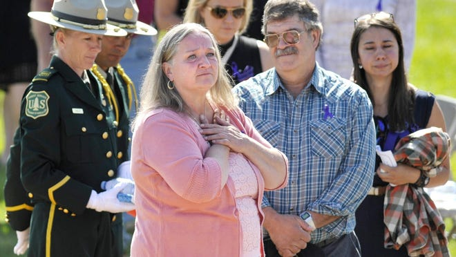 Fallen U.S. Forest Service firefighter Justin Beebe's parents Betsy, front, and Sheldon Beebe of Bellows Falls, Vt., look out over the crowd before memorial service for Justin Saturday, in Missoula, Mont. He was killed Aug. 13, while battling a wildfire.