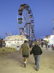 A couple walks down the midway at the Sheboygan County Fair.