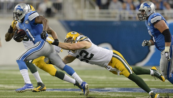Green Bay Packers linebacker Clay Matthews (52) tries to tackle Detroit Lions running back Reggie Bush (21) during the third quarter of Sunday's game at Ford Field in Detroit.