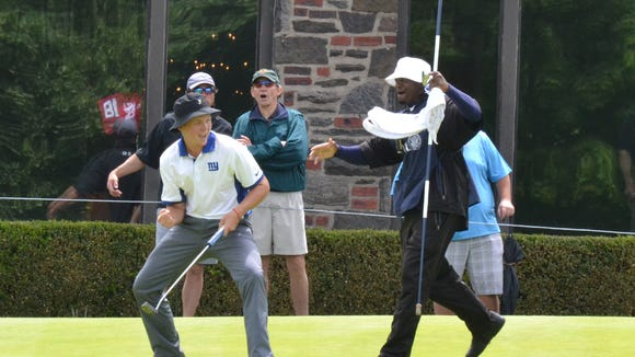 Benjamin Baxter and Winged Foot caddie Duane Cunningham celebrate a 60-foot birdie make that closed out a Round of 16 win Tuesday at the U.S. Amateur Four-Ball Championship.