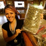 Crystal Young, who manages the CannaMedicine Marijuana Dispensary in Salem, poses with some of the marijuana that will be sold next week when the recreational sale of pot becomes legal in Oregon. Photo taken on Thursday, Sept. 24, 2015, Salem, Ore.