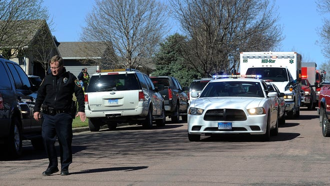 A procession of police and fire department vehicles led by Valley Springs Fire & Rescue escorts the ambulance to the coroner's office in Sioux Falls on Monday morning after a Sunday house fire claimed the lives of a homeowner and a volunteer firefighter in Brandon.