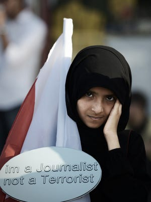 """A girl in Bahrain holds a placard reading """"I'm a Journalist not a Terrorist"""" during an anti-government protest in the village of Sitra, south of Manama."""