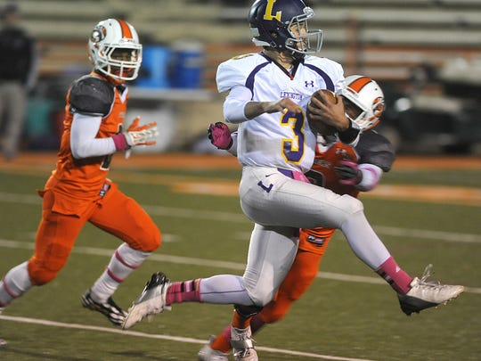 Lexington QB Joey Vore tries to leap out of the grasp