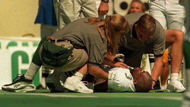 MSU football staff attend to Amp Campbell after he was injured on Sept. 5, 1998 at Oregon.