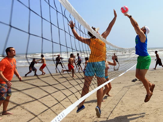 Beach goers play a game of volleyball during spring