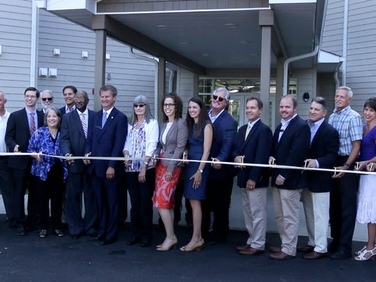 Officials from local government, KCDC, development partners and other agencies assembled for the ribbon-cutting on the Residences at Five Points, a 90-unit complex for the elderly and disabled.