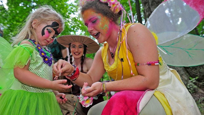 Evee Smith, 3, of Centerville, Tenn., left, is entertained by Shelby Dietrich, right, and Esther Cancasci during the 30th annual Tennessee Renaissance Festival in Arrington on Sunday.