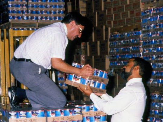 Two men handle cases of soup at the Progresso plant in 1989.