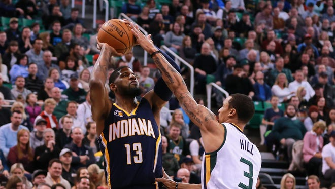 Indiana Pacers forward Paul George (13) shoots the ball over Utah Jazz guard George Hill (3) during the first quarter at Vivint Smart Home Arena.
