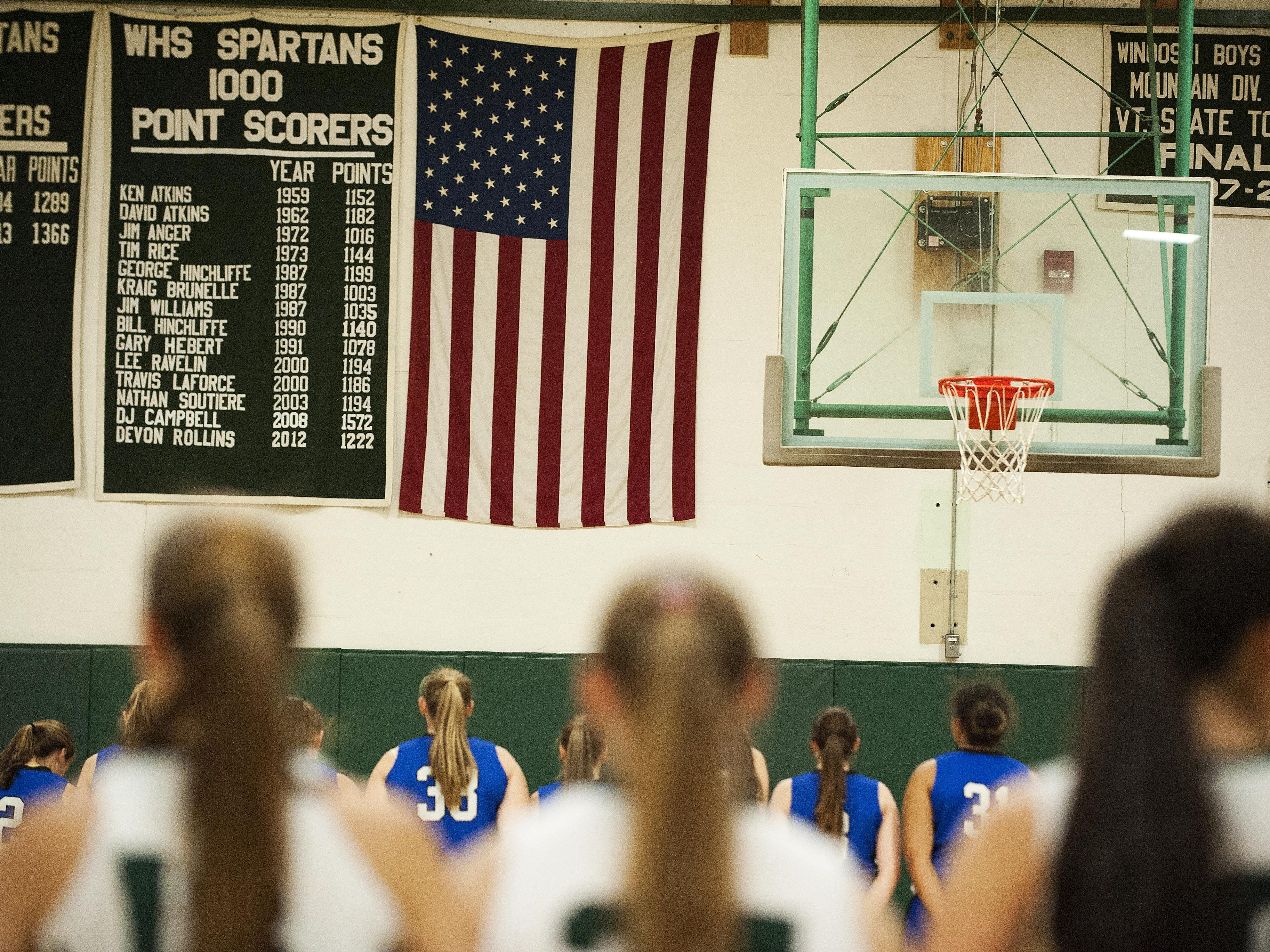 The teams line up to listen to the National Anthem before the start of the girls basketball game between Vergennes and Winooski at Winooski High School on Wednesday night.