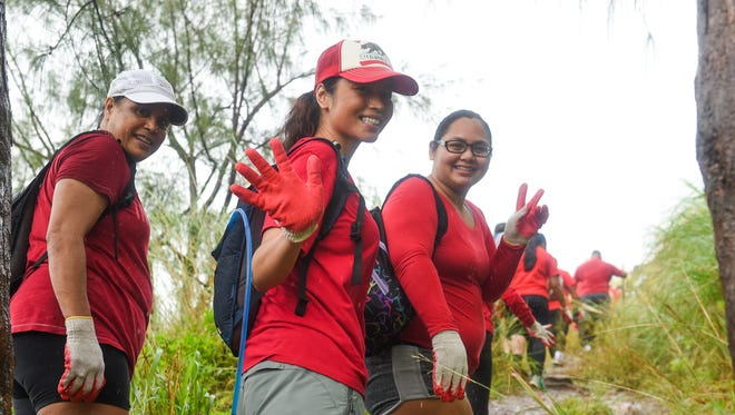 Bridal Boot Camp recruits Gennie-May Whitt, center, and Holi Tainatongo, right, wave farewell to the camera before their Mt. Lam Lam and Mt. Jumulong Manglo climb in Umatac on Jan. 28, 2017.