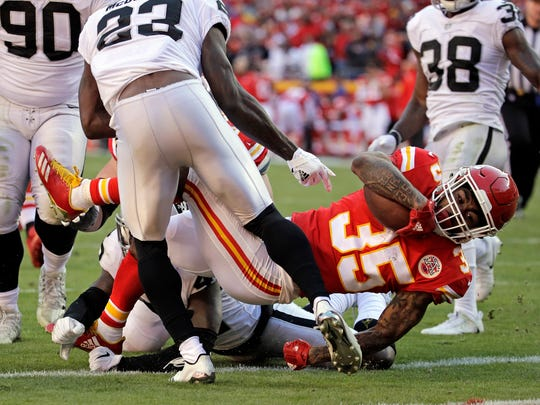 Kansas City Chiefs running back Charcandrick West (35) scores a touchdown behind Oakland Raiders cornerback Dexter McDonald (23) during the second half of an NFL football game in Kansas City, Mo., Sunday, Dec. 10, 2017.