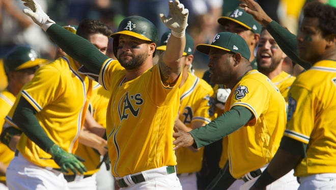 Oakland A's first baseman Yonder Alonso, center, celebrates a walk-off win over the Detroit Tigers on Sunday.