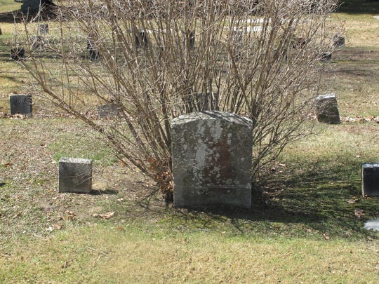 The work at Isaac Prince's gravestone entailed removing the bush, and raising the monument and its base out of the ground.