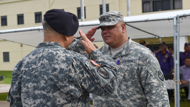 Sgt. 1st Class Peter Crisostomo salutes Brig. Gen. Roderick Leon Guerrero after being awarded the Purple Heart during the Guam National Guard Retreat Ceremony at the National Guard Readiness Center in Barrigada on Aug. 7.