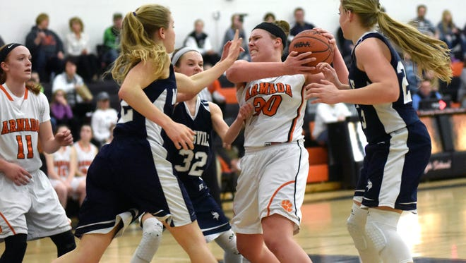 Armada Tigers' Bethany Ruczynski battles for possession Monday, Feb. 27, during girls district basketball action against Marysville at Armada High School.