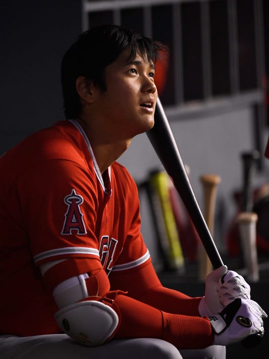 Los Angeles Angels starting pitcher Shohei Ohtani, of Japan, sits in the dugout during the second inning of a preseason baseball game against the Los Angeles Dodgers, Monday, March 26, 2018, in Los Angeles. (AP Photo/Mark J. Terrill)