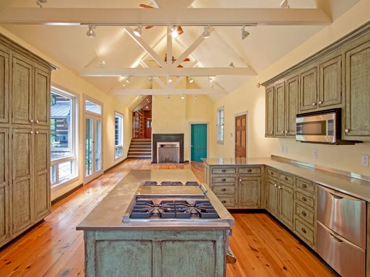 A new kitchen and gathering room were added shortly after the Hiatts bought the property. The custom cabinets were given an aged finish that matches an antique cupboard that the couple had.