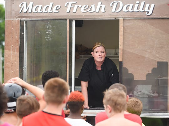 Jennifer Yeoman from the State of the Sandwich food truck takes orders of hot dogs from hungry children at Grant Middle School during one of the four stops the Marion Police Department made Tuesday throughout the community.