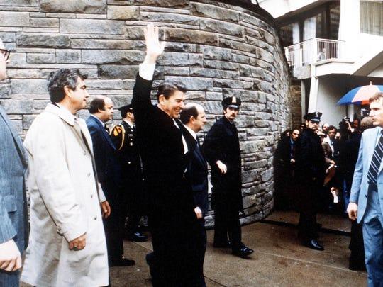 President Ronald Reagan moments before an assassination attempt by John Hinckley Jr. Jerry Parr is to the left in the white trench coat.