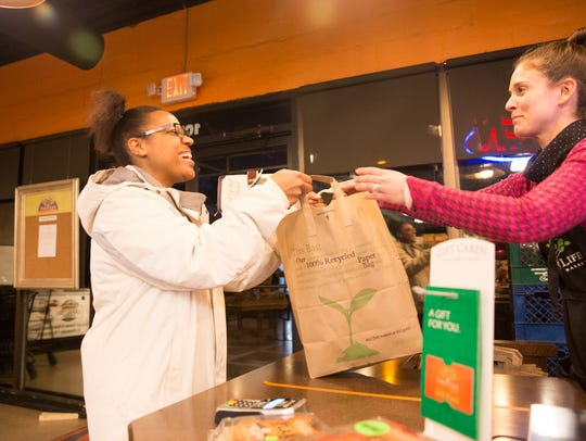 From left, customer Candace Holland purchases groceries