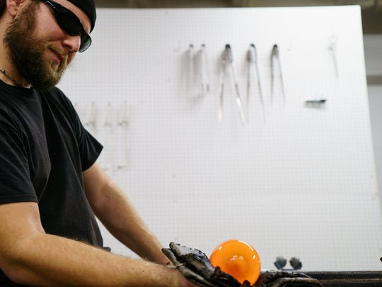 Glass blower Jesse Ahrendsen of Des Moines, works on