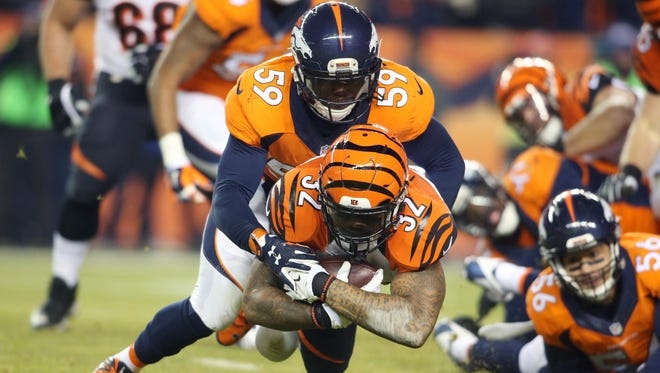 Cincinnati Bengals running back Jeremy Hill (32) is tackled by Denver Broncos inside linebacker Danny Trevathan (59) during the first half at Sports Authority Field at Mile High.