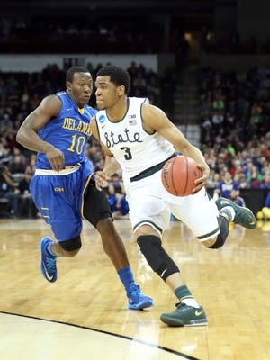 Alvin Ellis III  of the Michigan State Spartans dribbles past Devon Saddler #10 of the Delaware Fightin Blue Hens during the second round of the 2014 NCAA Men's Basketball Tournament at Spokane Veterans Memorial Arena on March 20, 2014 in Spokane, Washington.