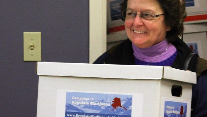 Mary Reff, a sponsor of an initiative to make recreational use of marijuana legal in Alaska, helps deliver thousands of signatures to the state Division of Elections office in Anchorage, Alaska, on Jan. 8, 2014.