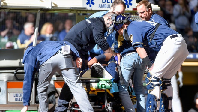 Brewers catcher Jett Bandy (right) checks on Rene Garcia after Garcia was injured in the ninth inning during the game against the Chicago White Sox and had to be carted off the field at Miller Park.