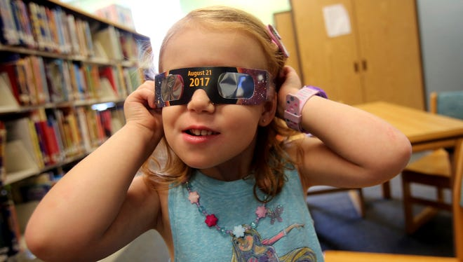 Make sure you have your special glasses for Monday's solar eclipse, such as these worn by 3-year-old Emmalyn Johnson at Mauney Memorial Library in Kings Mountain, North Carolina.