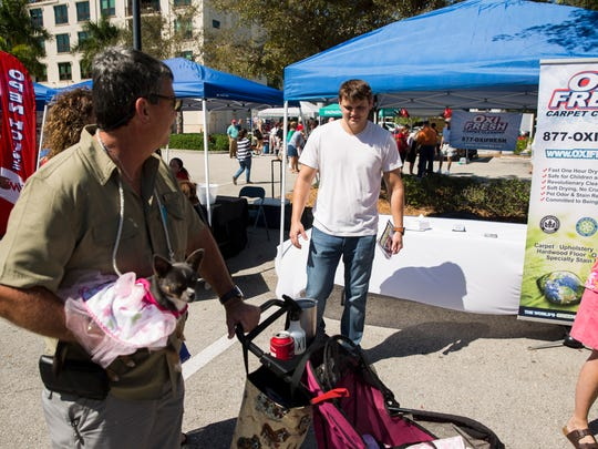 Charles Lawson, 27, center, greets Dominique Colas and his Chihuahua Zora as well as other passers-by while representing his Oxi Fresh Carpet Cleaning franchise during the fifth annual Woofstock event hosted by the Naples Humane Society at Mercato on Sunday, March 26, 2017, in North Naples. The Naples High graduate and Iraq War veteran is a new franchise owner of the eco-friendly carpet cleaning business in Naples.
